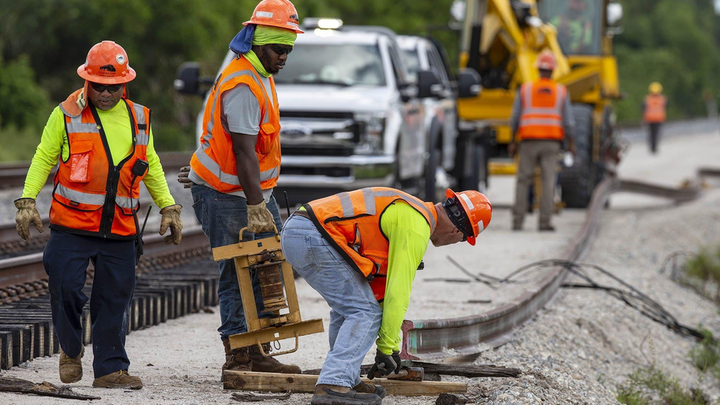 Brightline construction crews position a rail north of Hood Road in Palm Beach Gardens, Friday, August 7, 2020. Brightline is adding a second set of tracks for their planned expansion to Orlando.